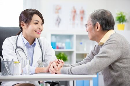 Female doctor see elder patient and console him not worry