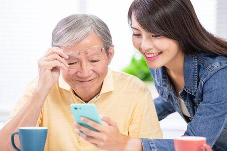 Hija joven enseñar al padre mayor a usar el móvil en casa