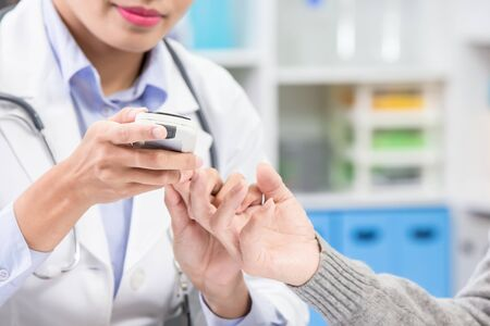 여의사는 노인 환자를 위해 혈당 검사를 한다 스톡 콘텐츠
