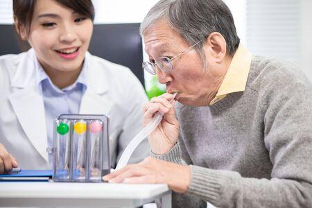 Elder patient has triflow training to improve vital capacity Stockfoto