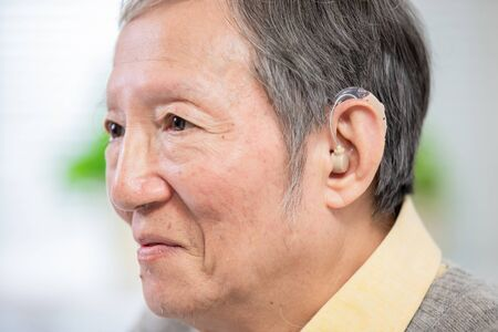 elder patient wear audiphone to improve his hearing