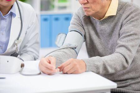 Doctora medir la presión arterial de un paciente anciano