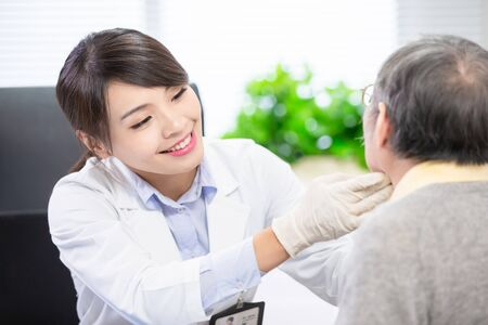 La dottoressa controlla attentamente la gola per il paziente anziano