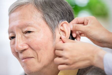 Doctor help elder patient wear audiphone to improve his hearing Фото со стока