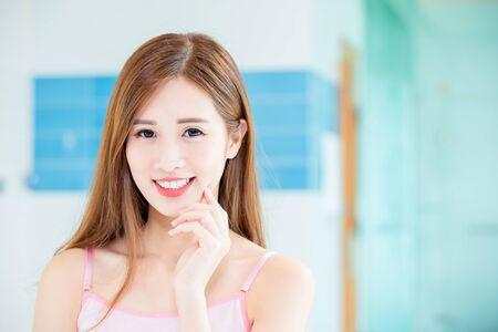 Schönheits-Hautpflegefrau berührt ihr Kinn und lächelt Sie zu Hause an