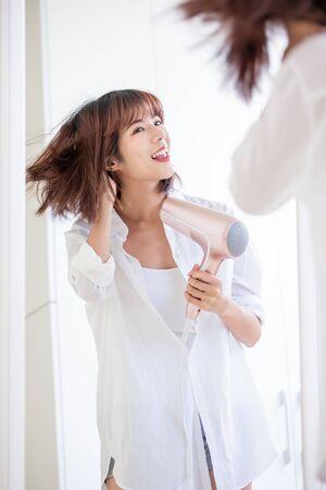 Hermosa joven secándose el cabello con secador
