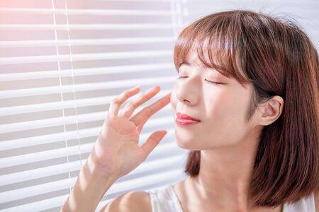 La mujer asiática joven del cuidado de la piel disfruta del sol y no le teme al bronceado