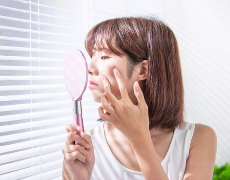 asian woman feel sad because her skin has acne prone Фото со стока