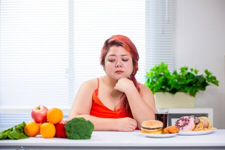 asian plus size woman think about choosing healthy food or not