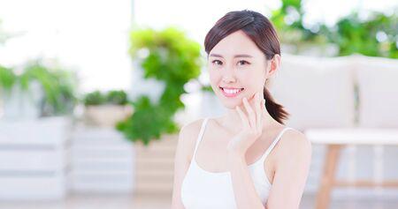 Glimlachende Aziatische vrouw die geniet van de huidverzorging en naar je glimlacht