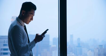 Asian businessman use cellphone and read message at night in the office