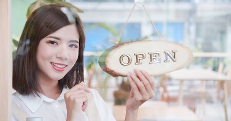 Pretty woman boss shopkeeper turning open sign in the morning