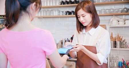 mobile payment concept - In the Cafe Woman Makes Takeaway Coffee For a Customer Who Pays by Contactless Phone to Credit Card System Zdjęcie Seryjne