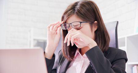 Aziatische vrouwelijke werknemer voelt zich moe en wrijft in de ogen Stockfoto