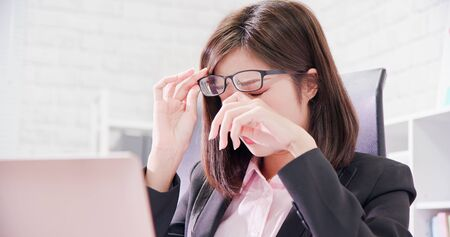 Une travailleuse asiatique se sent fatiguée et se frotte les yeux Banque d'images