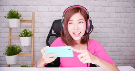 Young asian internet celebrity gamer girl introduce online mobile game to fans with smart phone and having live stream 版權商用圖片