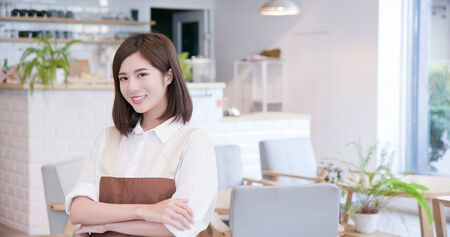 young asian shopkeeper smile to you in her restaurant Imagens