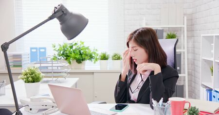 Asia woman worker feel tired and rubbing eyes Imagens