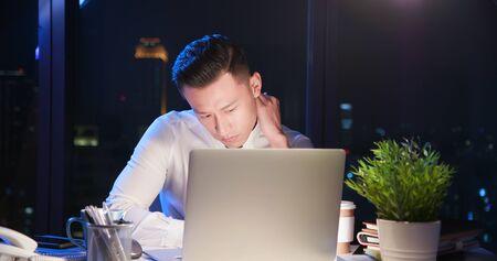travail d'heures supplémentaires d'homme d'affaires asiatique et se frottant le cou au bureau