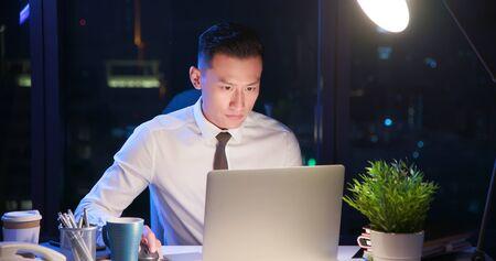 Hombre de negocios asiático trabajar horas extras solo en la oficina