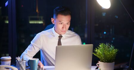 un homme d'affaires asiatique fait des heures supplémentaires seul au bureau