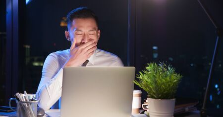 asian businessman overtime work and covering mouth to yawn Banco de Imagens