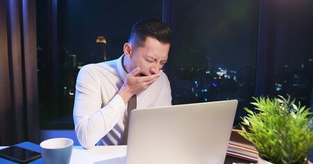 asian businessman overtime work and cover his mouth to yawn