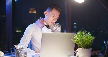 un homme d'affaires asiatique fait des heures supplémentaires et masse son épaule au bureau