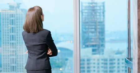 businesswoman look outside through the window and ponder