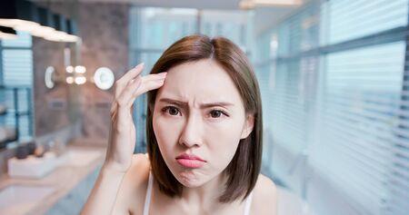 Aziatische jonge vrouw maakt zich zorgen over haar droge huid