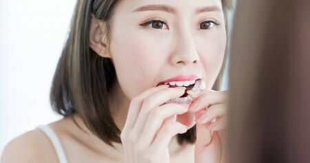 beauty woman look at the mirror and take off the invisible braces