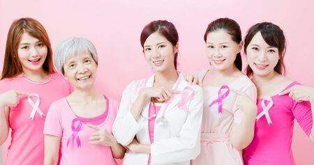 Doctor and women with breast cancer prevention show ribbon on the pink