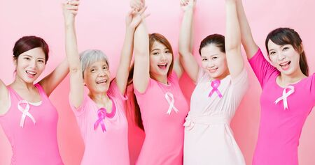 Women hands up with breast cancer prevention on the pink Stock Photo