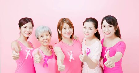 Women with breast cancer prevention and show thumb up on the pink