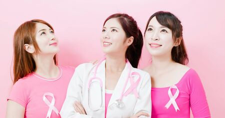 Doctor and women with breast cancer prevention look up forward on the pink Stock Photo