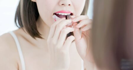 Young woman look at the mirror and take off the invisible braces