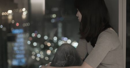 Young woman feel depressed by window and weeping in the night