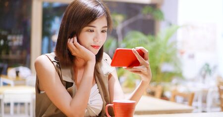 Woman watch video by cellular in coffee shop