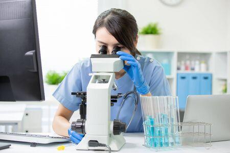 Asian young female veterinarian check illness with microscope 版權商用圖片