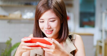 Young woman play mobile game happily in coffee shop 版權商用圖片 - 129774739