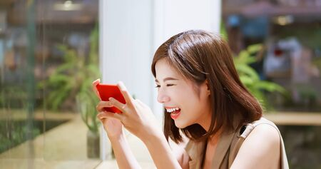 Young woman play mobile game happily in coffee shop