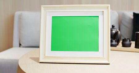 close up of photo frame with green copys space on table at home