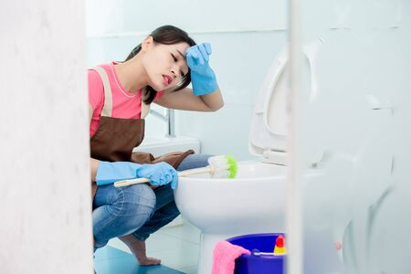 asian woman brush the toilet and wipe sweat on head 写真素材