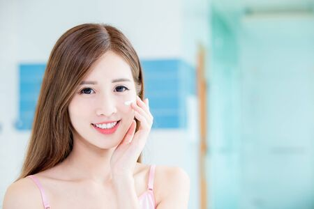 Beauty skin care woman apply cream on her face