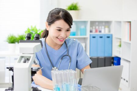 asian young femalie veterinarian use laptop with smile