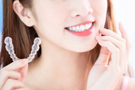 Beauty asian girl touch her chin and use invisible braces in front of mirror