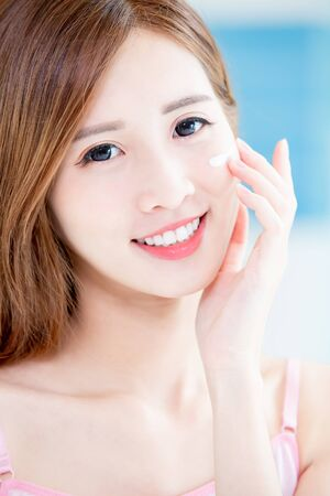 close up of beauty skin care woman apply cream on her face