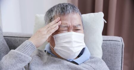 asian eldely sick man feel headache with mask lying on the sofa at home