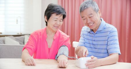asian elder couple use manometer to test blood pressure happily at home 版權商用圖片
