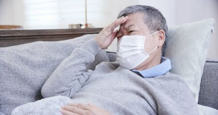 asian eldely sick man feel headache and wear mask lying on the sofa at home